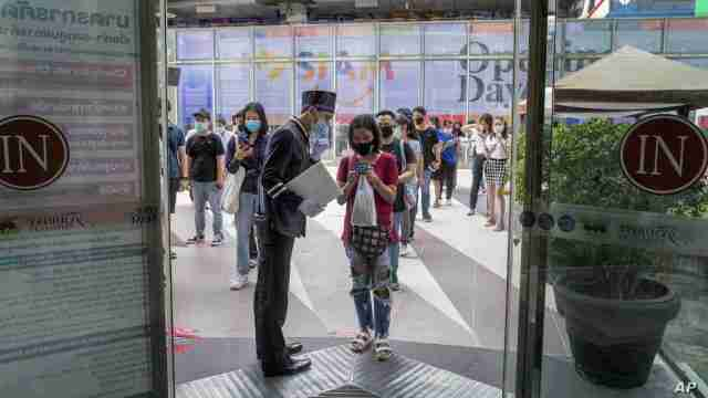 A woman displays her phone to doorman, to conform using a mobile application to help contact-tracing at the entrance to the upmarket shopping mall Siam Paragon in Bangkok, Thailand, Sunday, May 17, 2020. Thai authorities allowed department stores, shopping malls and other businesses to reopen from Sunday, selectively easing restrictions meant to combat the coronavirus. (AP Photo/ Gemunu Amarasinghe)