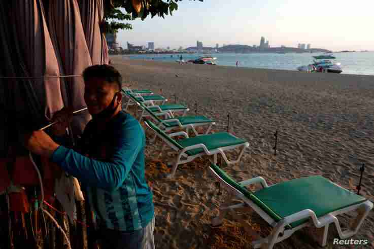 A man collects his umbrellas on an almost empty beach which usually crowed with tourists following the coronavirus disease (COVID-19) outbreak in Pattaya.