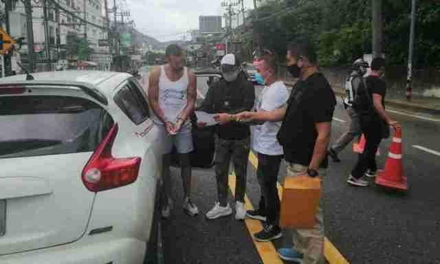 French national Elies Guenez, far left, is presented with a warrant as he is arrested in Phuket Tuesday.