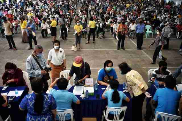 People sit in long lines as they wait to file complaints for not yet receiving the 5,000 Thai baht (150 USD) financial assistance for those whose income is impacted by the COVID-19 coronavirus outbreak, as others (front) file their documents, in front of the Public Relations Department in Bangkok on May 7.