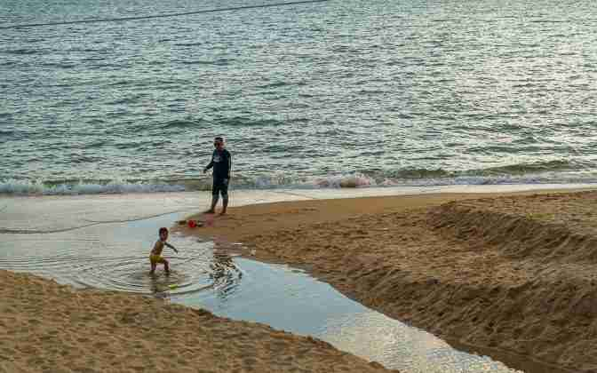 A man watches his youngster play in the shallow water left in the storm-created channel through Jomtien Beach on Sunday.