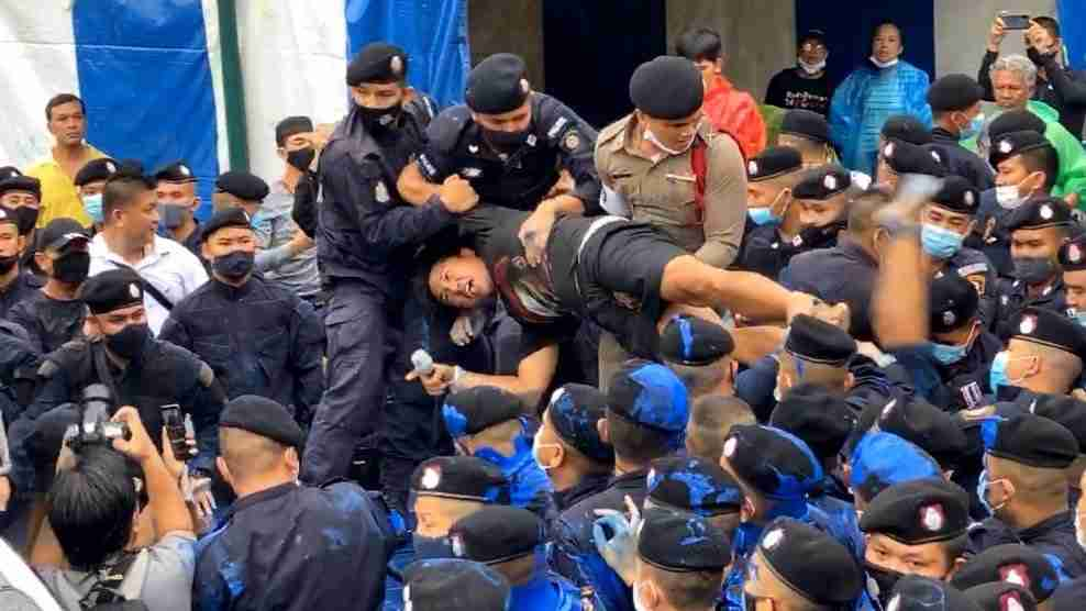 Police arrest an organizer of an Oct. 13 anti-government protest near the Democracy Monument in Bangkok Tuesday.