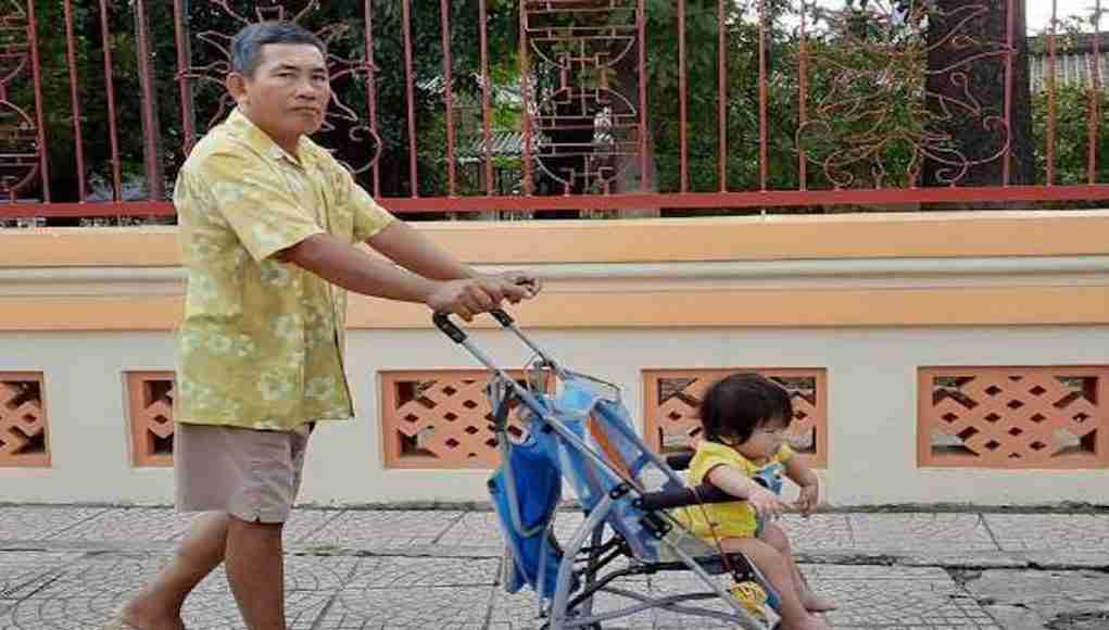 A man pushes a stroller on a street in Ho Chi Minh City. Many men have given up their jobs to look after their children so that their spouses can pursue careers. (Photo: UCA News)
