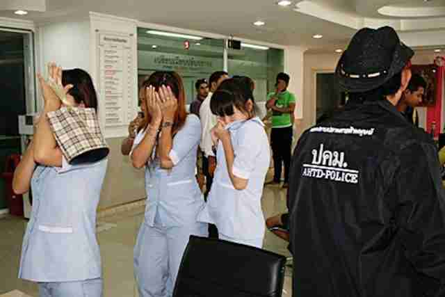 Employees hide their faces after their illegal abortion clinic was raided in Pattaya. (Photo: Pattaya Mail, with permisson)