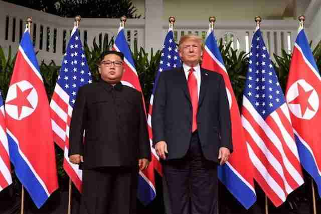 U.S. President Donald Trump poses with North Korea's leader Kim Jong Un at the start of their 2018 US-North Korea summit, at the Capella Hotel on Sentosa island in Singapore.