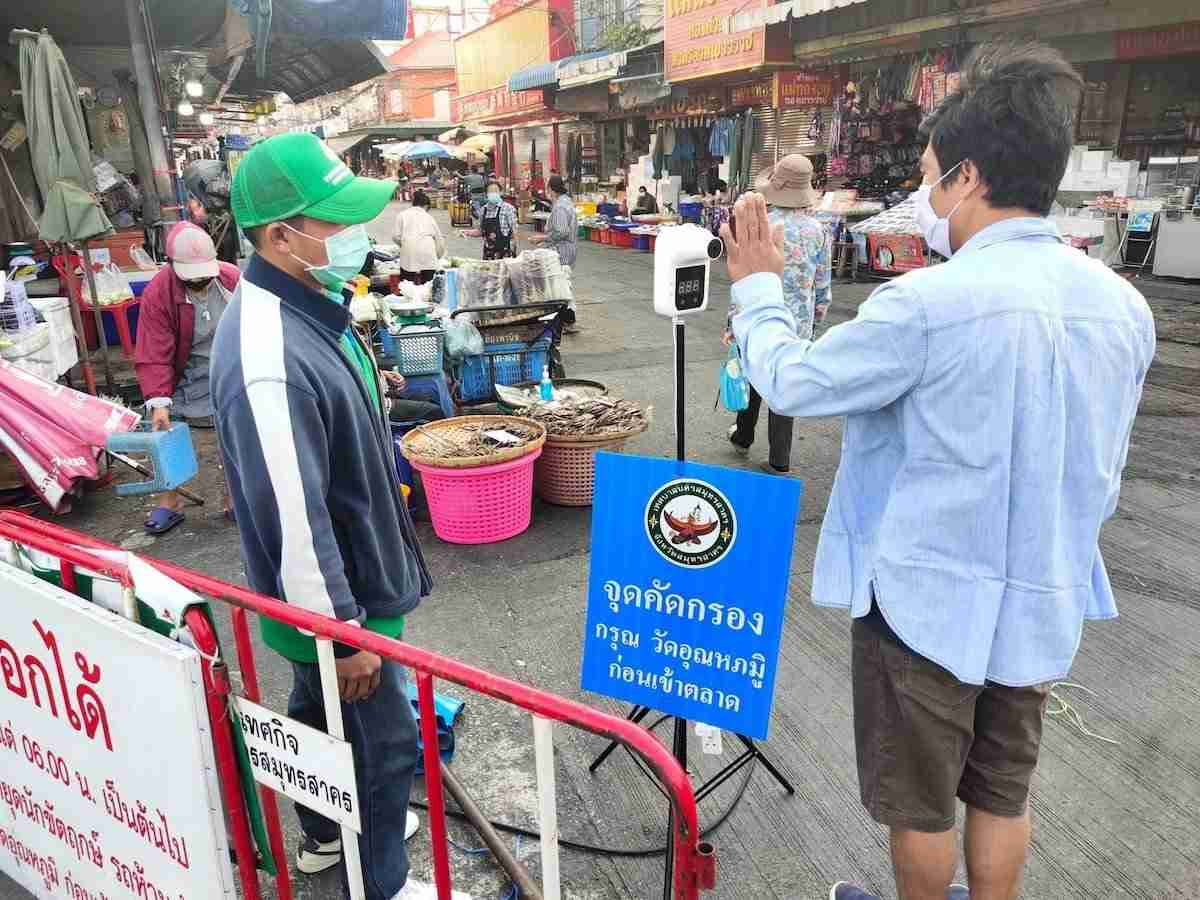 Shoppers to the Mahachi fresh market in Samut Sakhon check their temperatures before entering.
