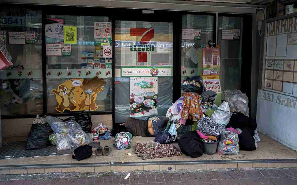 A homeless person sleeps amid her belongings and rubbish piled outside a closed 7-Eleven store in Pattaya in August 2020. (Photo: Bangkok Herald)