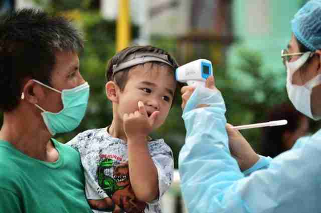 A young resident of the Bangkok's Klong Toey community has his temperature taken as he takes part in testing for the Covid-19 novel coronavirus