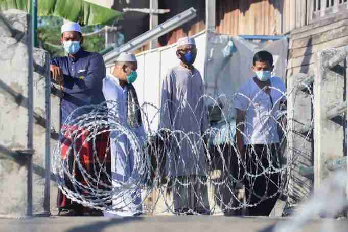 Migrant workers wearing face masks look on from behind barbed wire fence set up by authorities to block off a camp in an effort to halt the spread of the Covid-19 coronavirus in the Beting Tanjung community in southern Thailand's Pattani province.