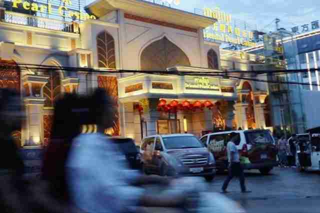 Women drive past a casino in Sihanoukville, a coastal city that has become a gambling boom town