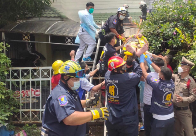 Firefighters bring German expat Benhard Hemker out of his burning Pattaya house after he stabbed and slashed himself. (Photo: Pattaya Mail, with permission)