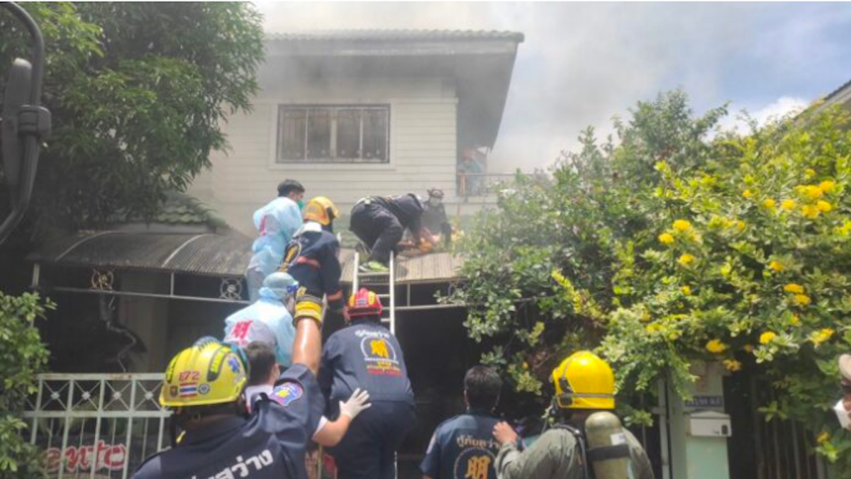 Firefighters treat German expat Benhard Hemker outside his burning Pattaya house after he stabbed and slashed himself. (Photo: Pattaya Mail, with permission)
