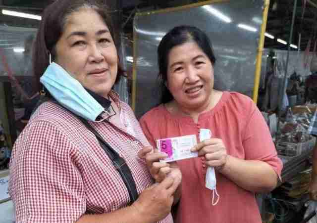 The winner of ฿30 million baht in the Sept. 16 government lottery in Chiang Mai, along with her security agent.