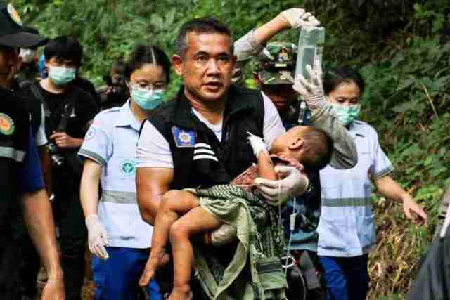 A Chiang Mai police officer carries the 2-year-old kidnapping victim alive out of a cave where she had been left three days.